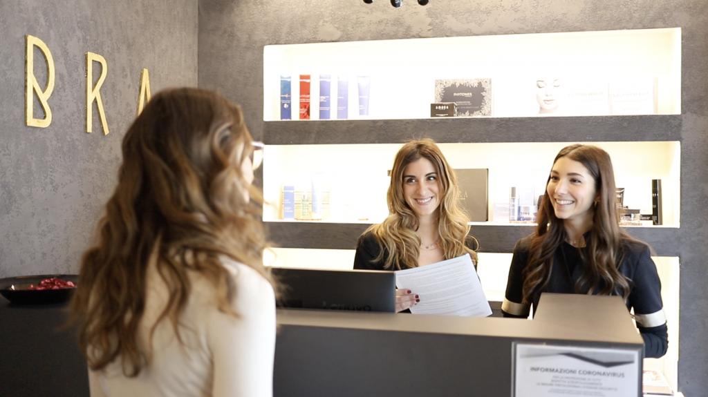 Due donne dietro al bancone di un centro estetico sorridono a donna di spalle
